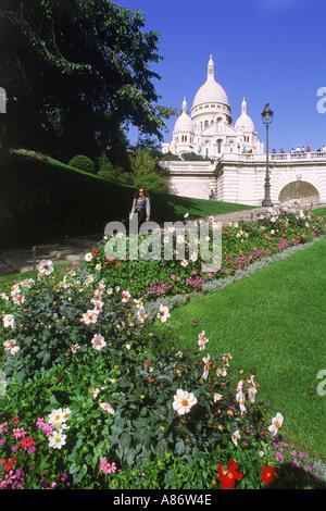 Flowers and tourist on steps below Sacré Coeur in Paris - Stock Photo