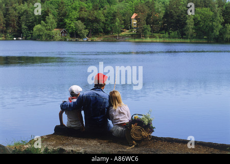 Dad and kids on lakeside fishing picnic in Sweden during summer - Stock Photo