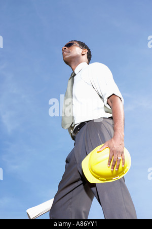 man standing in open air wearing dark glasses, carrying hard hat and plans - Stock Photo