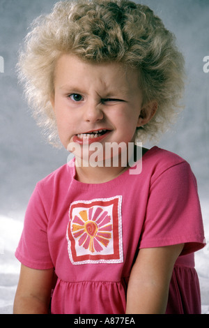A cute little blond girl 4-6 year old wearing pink winking making a funny face pulling faces ugly fun mouth POV - Stock Photo