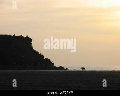 Horse and rider on the beach at sunset. UK - Stock Photo