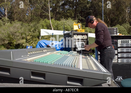 Sound technician prepares an audio console for an outdoor concert - Stock Photo