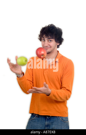 Young man in his late teens, casually dressed, playing with two apples and smiling at the camera. - Stock Photo
