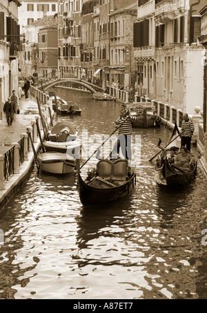 Gondolas and gondoliers in Venetian canal, Venice, Italy. - Stock Photo