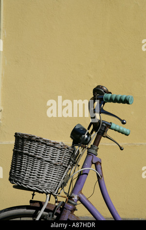 Bicycle with basket against wall, close-up - Stock Photo