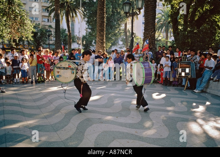 Native Chilean street performers entertain spectators with dancing and bass drums in Parque Italia Valparaíso Chile - Stock Photo