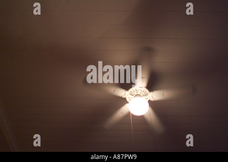 A rotating fan on bedroom ceiling with motion blurr - Stock Photo
