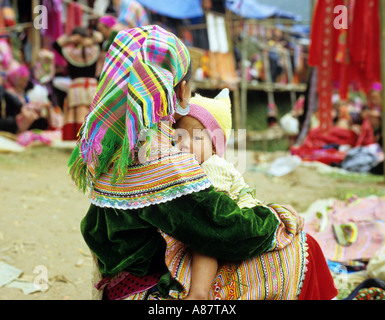 Back view of seated Flower Hmong woman in traditional dress with a baby on her lap, at the Saturday market, Can - Stock Photo