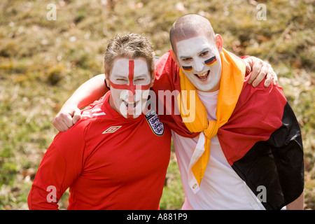 England and German football fans embracing each other in good spirit, happy smiling faces painted with national - Stock Photo