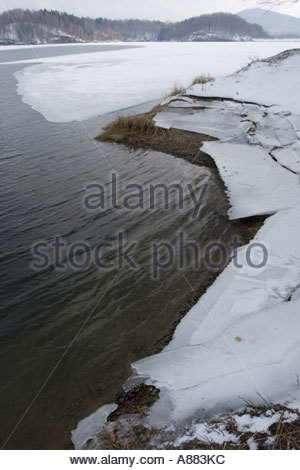 Late Winter breaking ice on peaceful lake - Stock Photo