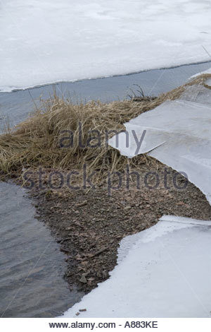 Late Winter breaking ice on peaceful lake close up - Stock Photo