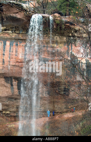 Several people standing behind one of the waterfalls on the Emerald Pool Trail in Zion Canyon in southern Utah - Stock Photo