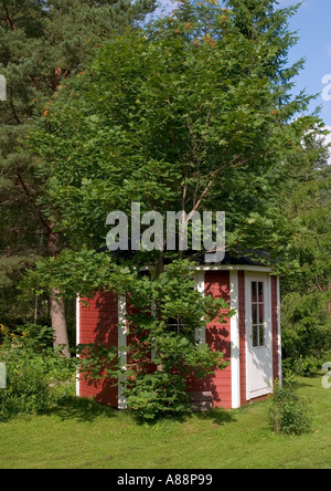Small, red, wooden outbuilding under maple tree in garden , Finland - Stock Photo