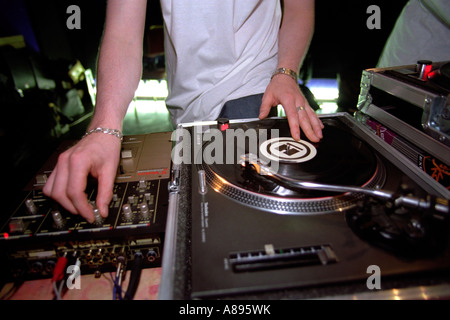 a dj mixing some records at a party or night club - Stock Photo