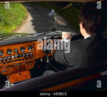 Chauffeur driving 1970 Daimler vanden plas DS 420 limousine - Stock Photo