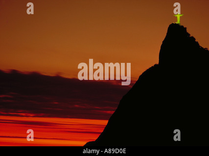 The statue of Christ the Redeemer Corcovado standing high on a hill at sunset against an orange sky in Rio de Janeiro - Stock Photo
