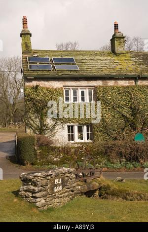 UK Yorkshire Wharfedale Threshfield Skirethorns traditional stone cottage with solar panels on roof - Stock Photo