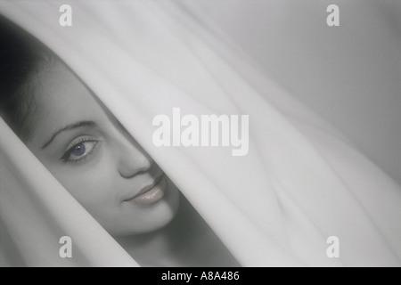Woman peering out through white curtains - Stock Photo