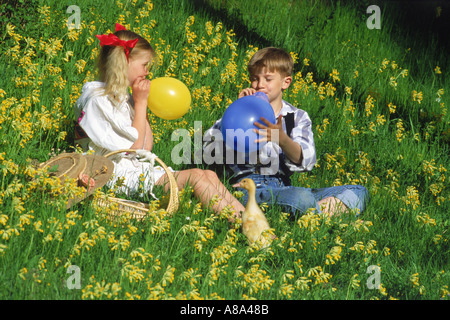 Boy and girl blowing up balloons with duck amid spring flowers in Sweden - Stock Photo