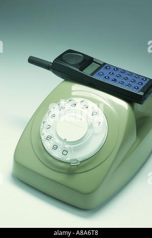 Mobile Phone on Telephone - Stock Photo