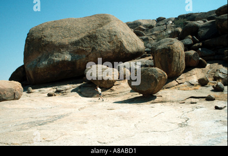 Running young man dwarfed by boulders in the Erongo Mountains Ameib Ranch Namibia Southern Africa - Stock Photo