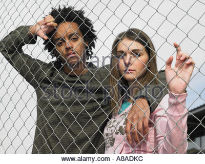 Two teenagers stood behind fence - Stock Photo