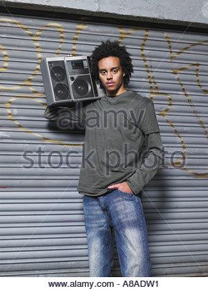 Teenage boy stood holding stereo - Stock Photo