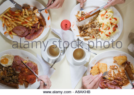 Four friends eating at cafe - Stock Photo