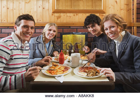 Four friends eating in cafe - Stock Photo