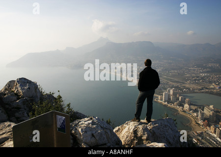 A man looks out at the view from Penan de Ifach above Calpe on the Costa Blanca in Spain - Stock Photo