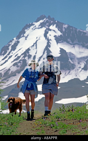 Two hikers and their Irish setter hike in the Oregon Cascades Three Sisters Wilderness Area - Stock Photo