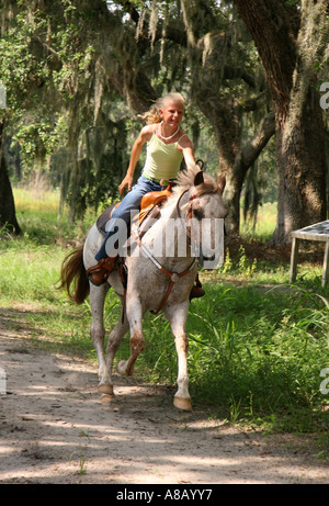 Teenage girl riding white horse down the path in the park. - Stock Photo