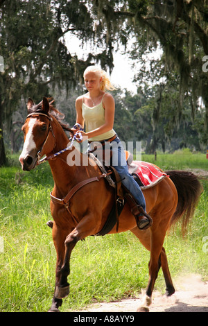Teenage girl riding brown horse down the path in the park. - Stock Photo