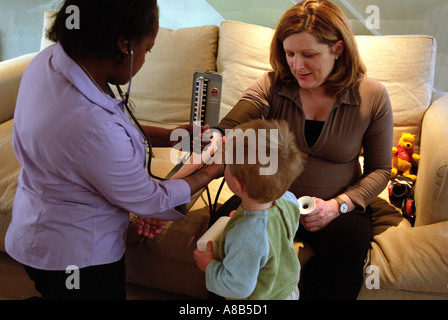 Midwife doing an anti-natal home visit and taking blood pressure of pregnant woman whilst toddler looks on. - Stock Photo
