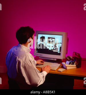 Man at computer looking into the past on his desktop personal computer - Stock Photo