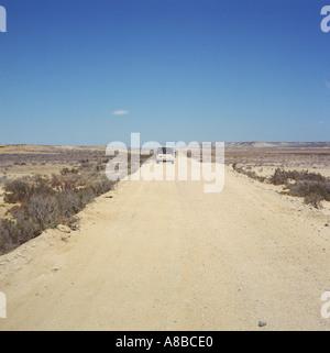 Long straight dirt road going straight with vehicle ahead through the Vizcaino Desert Baja California Sur Mexico - Stock Photo