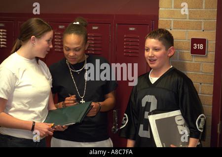 Students age 14 talking in front of school hallway lockers. Golden Valley Minnesota USA - Stock Photo