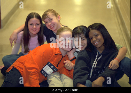 Girls age 15 showing affection for each other in school hallway. Golden Valley Minnesota USA - Stock Photo
