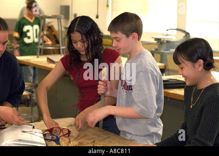 Students age 14 finishing shop pieces with file in school classroom. Golden Valley Minnesota USA - Stock Photo