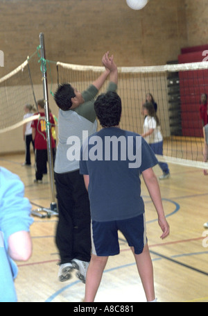 Students playing volleyball in gym class age 14. Golden Valley Minnesota USA - Stock Photo