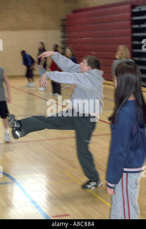 Student hitting volleyball over net age 14. Golden Valley Minnesota USA - Stock Photo