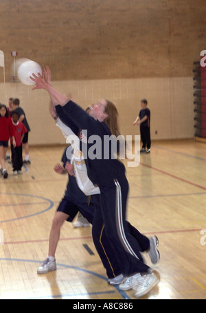Student pushing the volleyball over the net age 14. Golden Valley Minnesota USA - Stock Photo