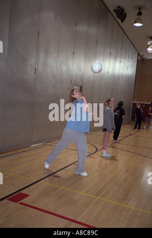 Student serving the volleyball during gym class age 14. Golden Valley Minnesota USA - Stock Photo