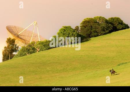 Satelite Dish pointing towards a pinkish hued sky while a horseman ride towards it - Stock Photo