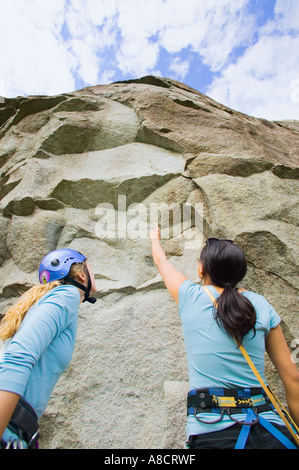 Two female rock climbers preparing to climb - Stock Photo