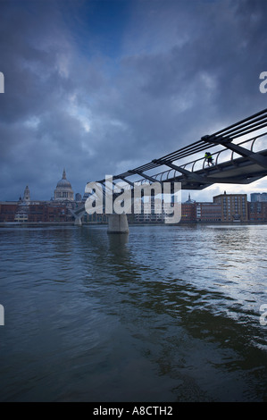 cyclist on the Millennium Bridge over the River Thames to St Pauls Cathedral London England UK - Stock Photo