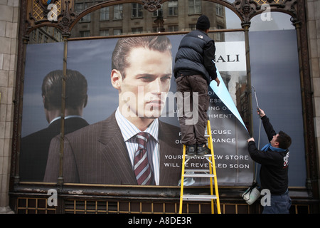 Poster men hang a covering over a window at the Savoy Taylors Guild in The Strand, London UK. - Stock Photo