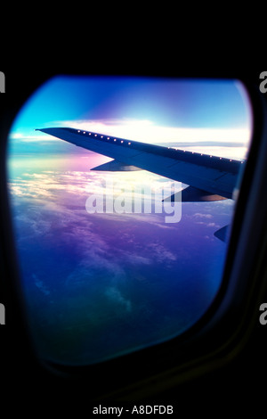 Airplane wing viewed through window of airline jet - Stock Photo