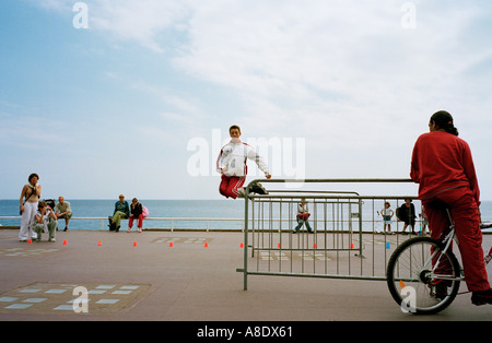 A rollerblader on the Promenade des Anglais, Nice, on the Cote d'Azur, France, shows his prowess by jumping a pole - Stock Photo