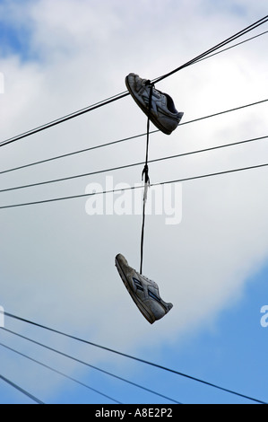 Shoes hanging from 'telephone wire' - Stock Photo